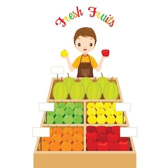Mężczyzna sklepikarz z dużą ilością owoców w zasobniku, zdrowe odżywianie