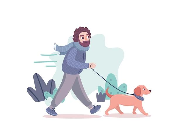 Mężczyzna spaceruje z psem jamnika po parku