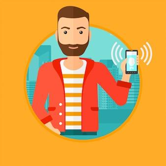 Mężczyzna trzyma dzwoniący telefon komórkowy.