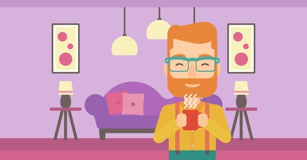 Mężczyzna trzyma filiżankę kawy.