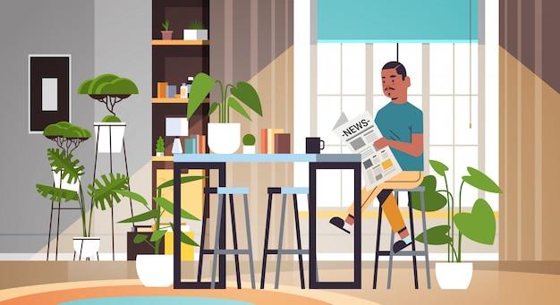 Mężczyzna trzyma gazetę czyta codzienne wiadomości prasa środki masowego przekazu facet siedzi przy stoliku w kawiarni