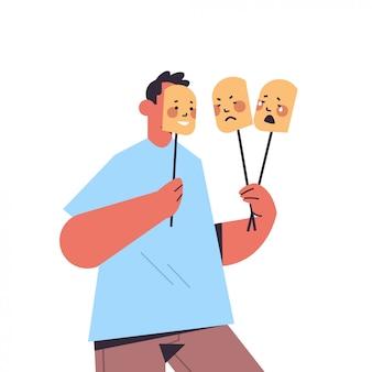 Mężczyzna trzyma maski z różnymi emocjami fałszywe uczucie depresji zaburzenia psychiczne