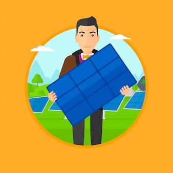 Mężczyzna trzyma panel słoneczny.