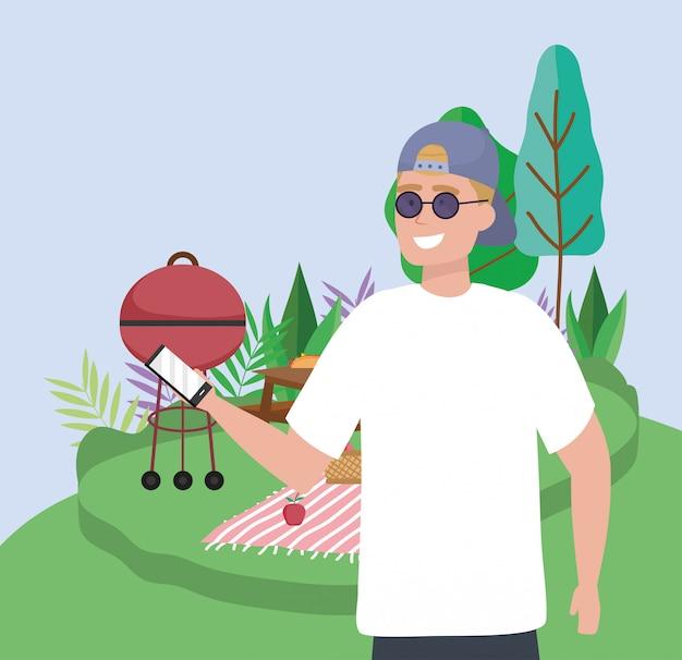 Mężczyzna trzyma smartphone grill koc koc campingowy piknik