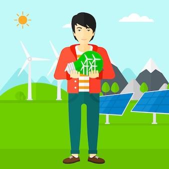 Mężczyzna trzyma żarówkę z wiatrakami wewnątrz