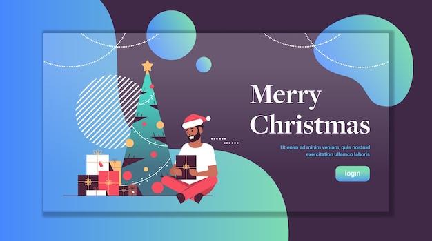 Mężczyzna trzymający prezent pudełko wesołych świąt szczęśliwego nowego roku wakacje uroczystość koncepcja afroamerykanin w kapeluszu mikołaja siedzi w pobliżu jodły płaska pełna długość kopia przestrzeń poziome wektor ilus