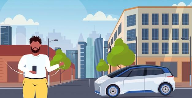 Mężczyzna używa smartphone aplikację mobilną online rozkazuje taxi dzielenia samochodu pojęcia transportu carsharing usługa nowożytnego miasta pejzażu miejskiego tła uliczny horyzontalny portret