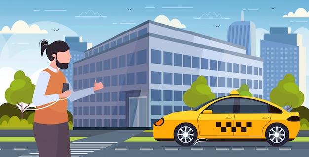 Mężczyzna używa smartphone mobilną aplikację zamawia taxi faceta łapania żółtej taksówki transportu usługa pojęcia nowożytnego pejzażu miejskiego tła horyzontalny portret