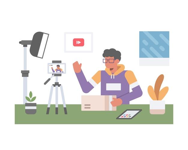 Mężczyzna vlogger rozpakowuje i ocenia produkt na żywo na youtube w studio