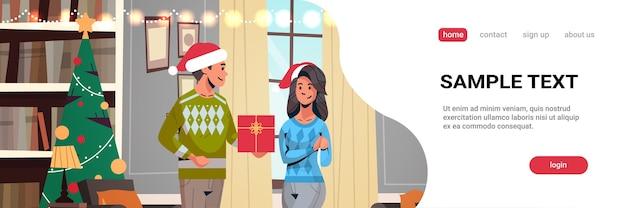 Mężczyzna w kapeluszu mikołaja daje prezent pudełko kobiecie młoda para świętuje wesołych świąt szczęśliwego nowego roku ferie zimowe koncepcja nowoczesny salon wnętrze strona docelowa