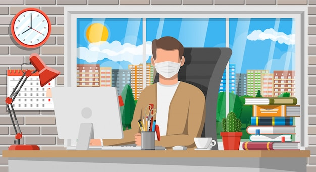 Mężczyzna w medycznej masce pracuje na jego komputerze