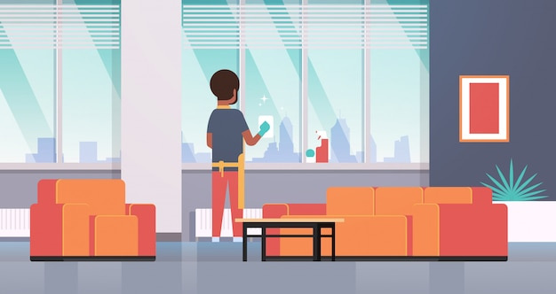 Mężczyzna w rękawiczkach i fartuchu do czyszczenia okien szmatką do czyszczenia sprayem widok z tyłu facet robi prace domowe koncepcja nowoczesne mieszkanie salon wnętrze pełnej długości poziomej