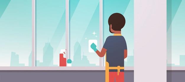 Mężczyzna w rękawiczkach i fartuchu do czyszczenia okien szmatką do czyszczenia sprayem widok z tyłu facet robi prace domowe koncepcja nowoczesne mieszkanie salon wnętrze portret poziomy