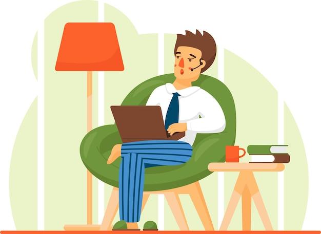 Mężczyzna w swobodnym stroju siedzi w domu w wygodnym fotelu i przegląda lub pracuje na laptopie na kolanach.