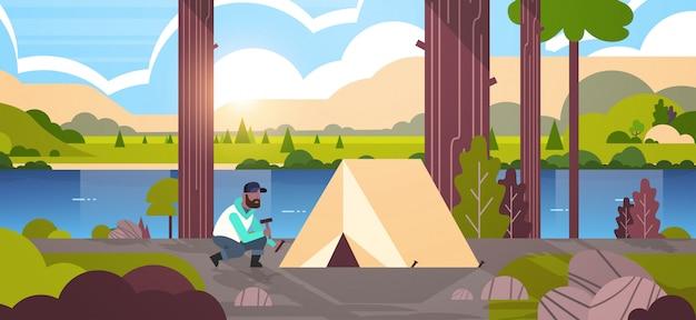 Mężczyzna wycieczkowicz obozowicz instaluje namiot przygotowywa dla obozuje wycieczkuje pojęcie wschodu słońca natury natury rzeki gór tła horyzontalnej pełnej długości