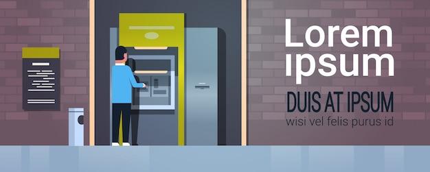 Mężczyzna wypłacający gotówkę za pośrednictwem bankomatu