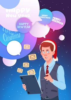 Mężczyzna z cyfrowej pastylki wysyła wiadomości powitanie z szczęśliwym nowym rokiem i wesoło bożymi narodzeniami przez