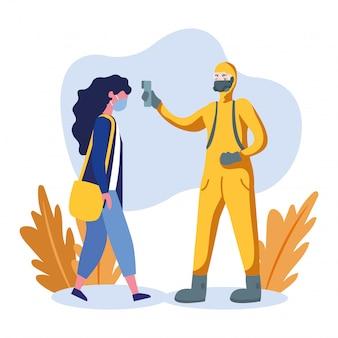 Mężczyzna z ochronnym kostiumem sprawdza kobiety temperaturę