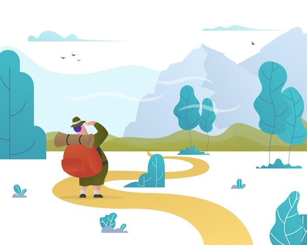 Mężczyzna z plecakiem patrzy w odległe góry.