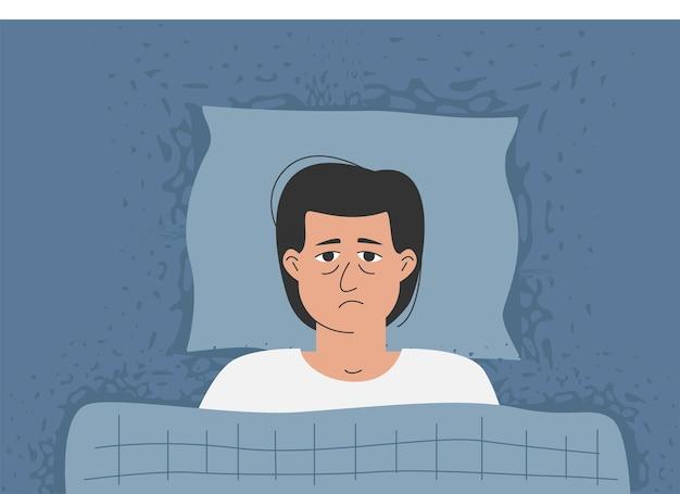 Mężczyzna z szeroko otwartymi oczami leży w łóżku, nie może spać.