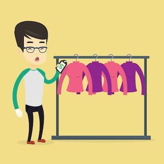 Mężczyzna zszokowany ceną w sklepie odzieżowym.