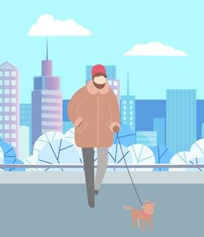 Mężczyznę idącego psa na smyczy w winter city park