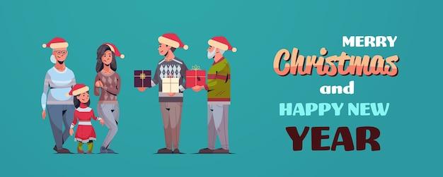 Mężczyźni dając prezent pudełka kobietom wielopokoleniowym rodzina w czapkach mikołaja świętuje wesołych świąt szczęśliwego nowego roku koncepcja ferii zimowych
