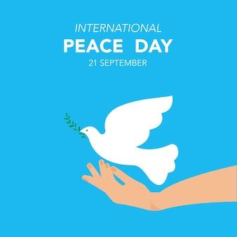 Międzynarodowy dzień pokoju gołąb wylatuje z jego ręki symbol pokoju wektor w płaskiej konstrukcji