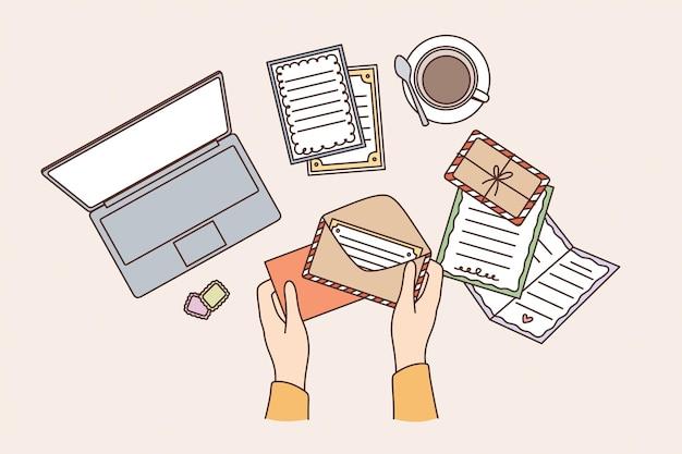 Miejsce pracy i koncepcja stołu. widok z góry ludzkich rąk wysyłających pocztówkę w kopercie na ilustracji wektorowych stołu roboczego