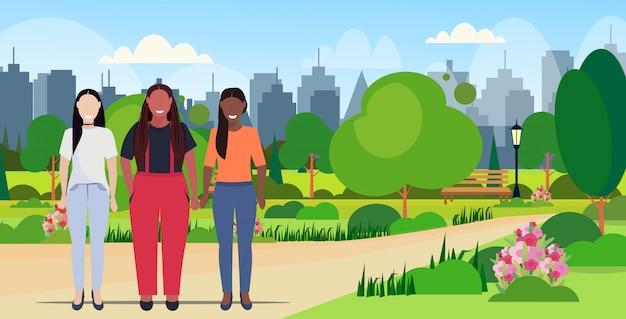 Miesza dziewczyny różnego ciało kształta postaci kobiety stoi wpólnie plenerowego miastowego parka pejzażu miejskiego tło folował długość horyzontalną
