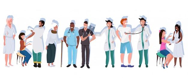 Mieszać biegowych lekarzy z pacjentami stojącymi razem pracowników szpitala w jednolitym zawodowym zawodzie opieki zdrowotnej medycyny pojęcie pełnej długości płaskiej poziomej