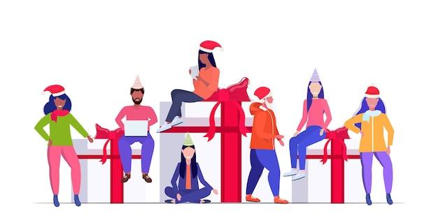 Mieszać ludzi rasy w czapkach mikołaja przygotowujących się do świąt bożego narodzenia i uroczystości nowego roku mężczyzn kobiety siedzących na prezentach prezentowe pudełka ferie zimowe