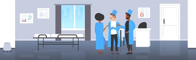 Mieszać rasy lekarzy drużyna dyskutuje podczas spotkania personelu medycznego kolegów w jednolitej pozyci wpólnie pracy zespołowej medycyny opieki zdrowotnej pojęcia nowożytnej sala szpitalnej wewnętrzny pełnej długości horyzontalny