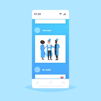 Mieszać rasy lekarzy drużyna dyskutuje podczas spotkania personelu medycznego kolegów w mundurze stoi wpólnie pracy zespołowej medycyny opieki zdrowotnej pojęcia smartphone ekranu mobilna aplikacja pełna długość
