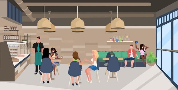 Mieszać rasy ludzi siedzących przy stolikach w kawiarni goście spędzający czas razem kelner obsługujący klientów nowoczesnej restauracji wnętrze płaskie poziome pełnej długości