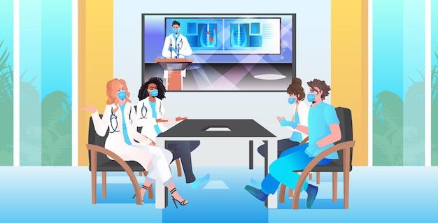 Mieszać zespół lekarzy wyścigowych z wirtualną konferencją specjalistów medycznych w maskach dyskutujących podczas rozmowy wideo