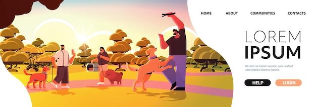 Mieszaj ludzi rasy spacerujących z właścicielami psów i uroczymi zwierzętami domowymi, które bawią się przyjaźnią z koncepcją zwierząt domowych