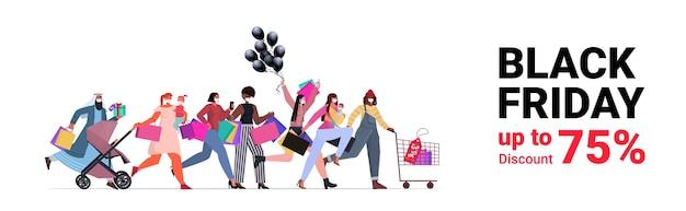 Mieszaj ludzi rasy w maskach ochronnych biegających z torbami na zakupy czarny piątek duża promocja sprzedaży rabat koronawirus koncepcja kwarantanny transparent