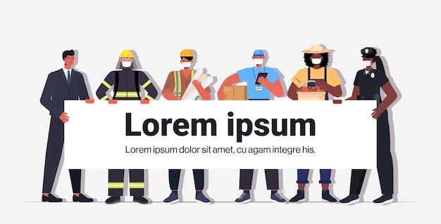 Mieszaj ludzi rasy z różnych zawodów, trzymając transparent święto pracy, mężczyźni kobiety noszący maski, aby zapobiec koronawirusowi