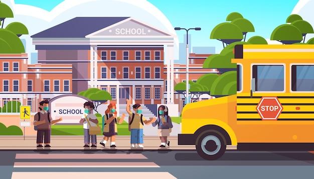 Mieszaj rasowe dzieci w wieku szkolnym noszące maski, aby zapobiec pandemii koronawirusa uczniom stojącym razem w pobliżu szkolnego autobusu