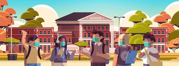 Mieszaj rasowe dzieci w wieku szkolnym noszące maski, aby zapobiec pandemii koronawirusa uczniowie stojący razem w pobliżu portretu budynku szkolnego