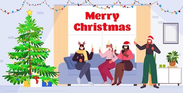 Mieszana rasa koleżanki w czapkach i maskach świętego mikołaja picie szampana nowy rok święta bożego narodzenia koncepcja uroczystości wnętrze salonu pełna długość napis pozdrowienia illustrati