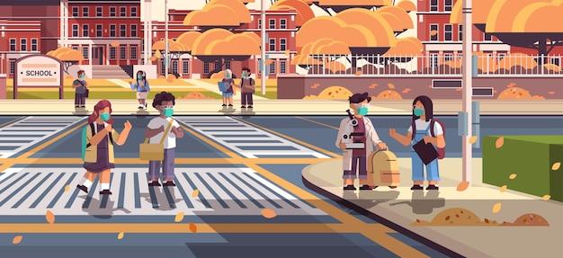 Mieszane rasy uczniowie w maskach przechodzący przez ulicę na przejściu dla pieszych uczniowie idący do szkoły pandemia koronawirusa