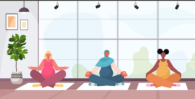 Mieszane wyścig kobiety w ciąży robi ćwiczenia jogi fitness szkolenia koncepcja zdrowego stylu życia dziewczyny medytuje razem nowoczesne wnętrze studia