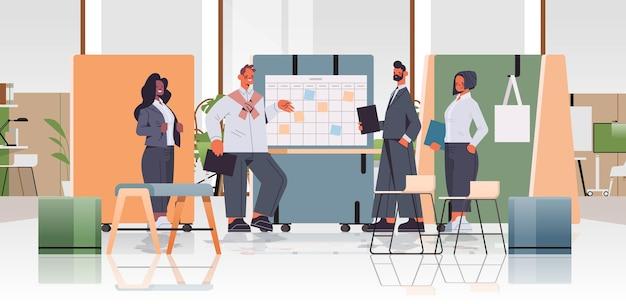 Mieszanka biznesmenów wyścigowych omawiających i pracujących podczas spotkania firmowego w koncepcji pracy zespołowej w centrum coworkingowym
