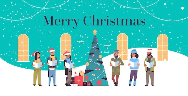 Mieszanka rasa ludzie czytający książki wesołych świąt szczęśliwego nowego roku święto uroczystość koncepcja mężczyźni kobiety w czapkach mikołaja stojących blisko dopasowanego drzewa poziome pełnej długości ilustracja wektorowa