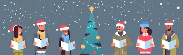 Mieszanka rasa ludzie czytający książki wesołych świąt szczęśliwego nowego roku święto uroczystość koncepcja mężczyźni kobiety w czapkach mikołaja stojących blisko dopasowanego drzewa poziomy portret wektor ilustracja