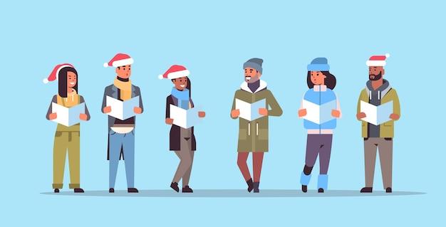 Mieszanka rasy ludzie czytający książki wesołych świąt szczęśliwego nowego roku koncepcja obchodów wakacji mężczyźni kobiety noszących czapki mikołaja poziome pełnej długości ilustracji wektorowych