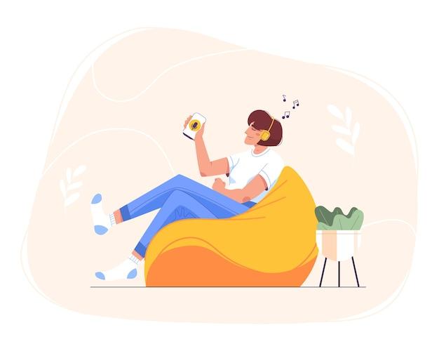 Mieszkanie szczęśliwy teen dziewczyna w słuchawkach, siedząc w domu w fotelu worek fasoli i przy użyciu smartfona do edukacji online. kobieta relaksująca się i słuchająca muzyki, podcastów audio, radia lub audiobooka na telefonie komórkowym