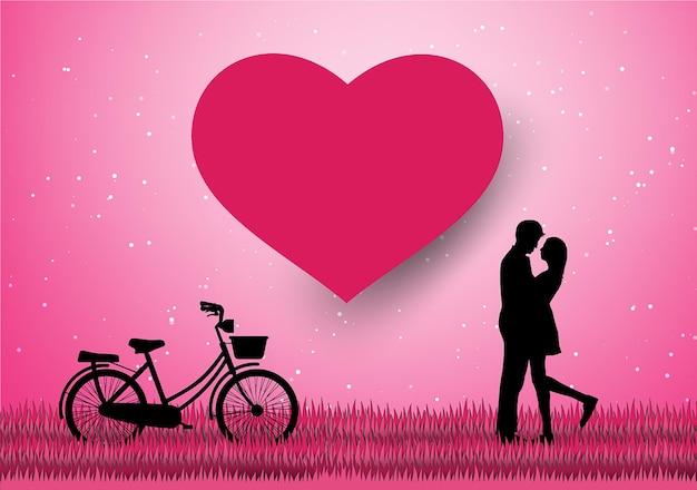Miłośnicy miłości i walentynek stoją na łąkach i papierowym kształcie serca